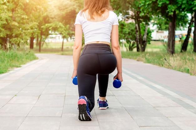 Mette in mostra la ragazza che fa gli esercizi con le teste di legno nel parco.