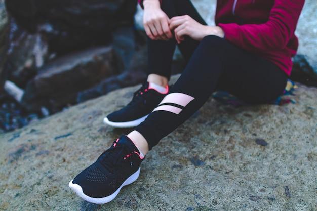 Mette in mostra la ragazza in scarpe da tennis che si siedono su una pietra e che riposano dopo un allenamento al tramonto. solitudine con natura, sport e stile di vita attivo