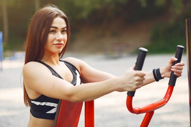 Mette in mostra la ragazza in un addestramento superiore nero in un parco dell'estate