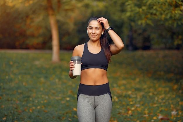 Mette in mostra la ragazza in un addestramento superiore nero in un parco di autunno