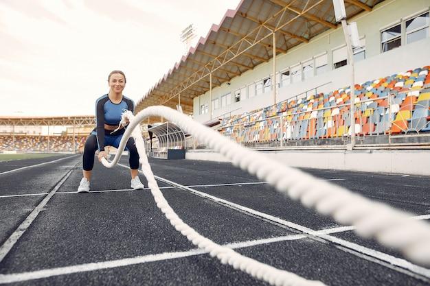 Mette in mostra la ragazza in un addestramento uniforme blu allo stadio con la corda