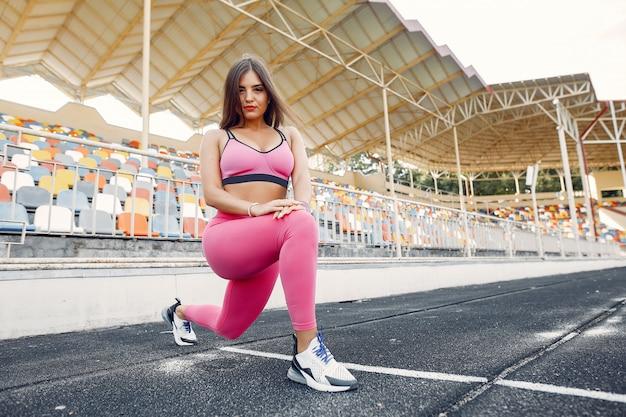 Mette in mostra la ragazza in un addestramento uniforme rosa allo stadio