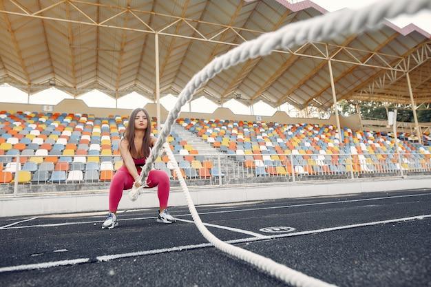 Mette in mostra la ragazza in un addestramento uniforme rosa con la corda allo stadio