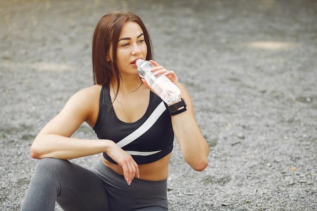 Mette in mostra la ragazza in vestiti di sport che beve un'acqua