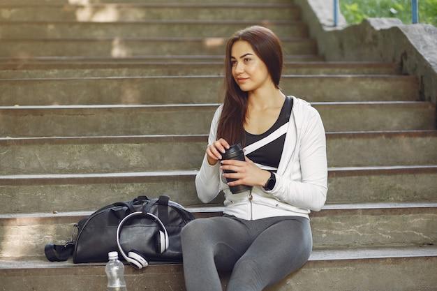 Mette in mostra la ragazza in vestiti di sport in una città