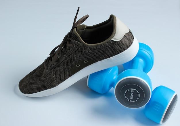 Mette in mostra le scarpe da tennis e le teste di legno sulla tavola bianca.