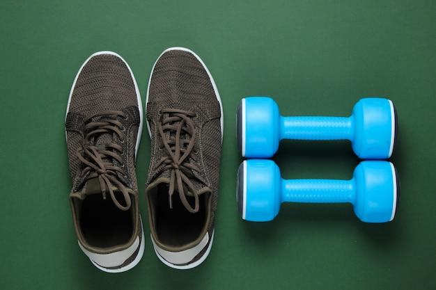 Mette in mostra le scarpe da tennis e le teste di legno sulla tavola verde.