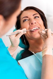 Mettere le parentesi graffe dentali ai denti della donna nello studio dentistico. il dentista esamina il paziente femminile con le parentesi graffe in studio dentistico. primo piano di una giovane ragazza attraente con parentesi graffe sui denti