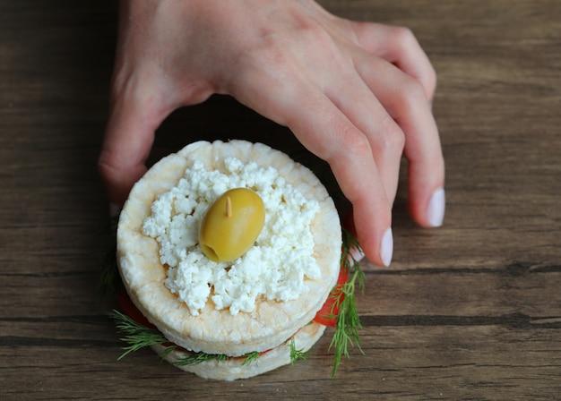 Mettere un hamburger cracker senza glutine su un tavolo di legno.