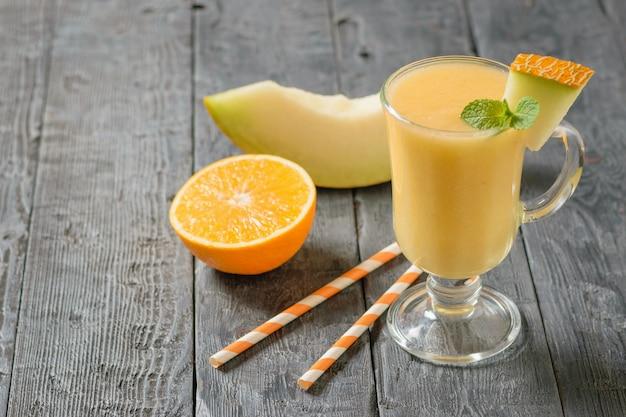 Mezza arancia, un pezzo di melone e una tazza di frullato su un tavolo di legno.