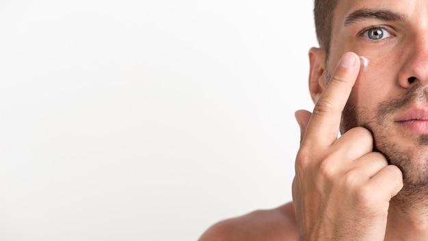 Mezza faccia del giovane senza camicia che applica crema sul suo fronte contro il fondo bianco