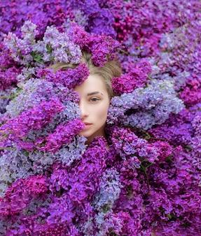 Mezza faccia della giovane ragazza bionda caucasica circondata da un sacco di lilla viola e viola, carta da parati, melodia di primavera