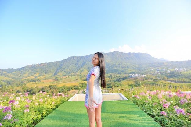 Mezza lunghezza della giovane donna asiatica sentirsi liberi con le braccia spalancate a bellissimi alberi e m
