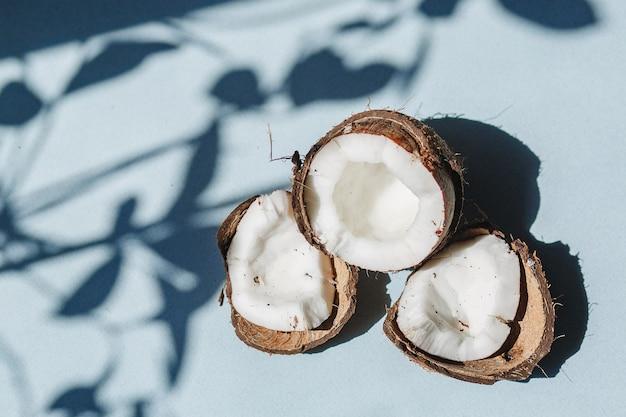 Mezza noce di cocco e pezzi di noce di cocco su sfondo blu.