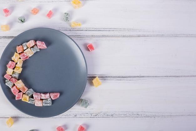 Mezzaluna colorata fatta con lukum sul piatto grigio sopra il tavolo di legno bianco