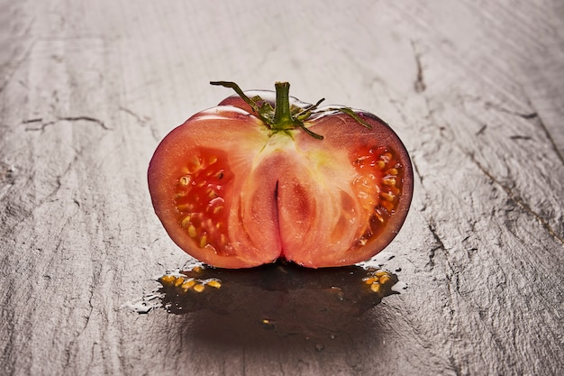 Mezzi pomodori maturi di raf su ardesia nera