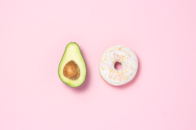 Mezzo avocado e ciambella su uno sfondo rosa. concetto di scelte alimentari. cibo utile o dannoso. minimalismo. vista piana, vista dall'alto.