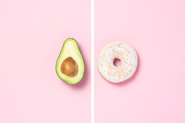 Mezzo avocado e ciambella su uno sfondo rosa. concetto di scelte alimentari.