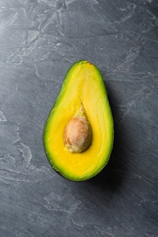 Mezzo avocado su sfondo scuro. concetto di cibo salute