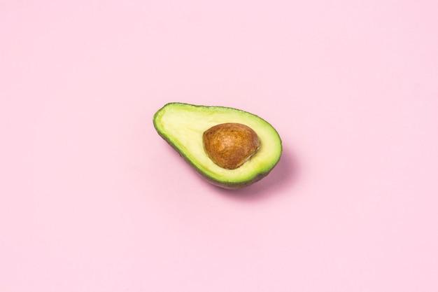 Mezzo avocado su uno sfondo rosa. concetto di mangiare sano.