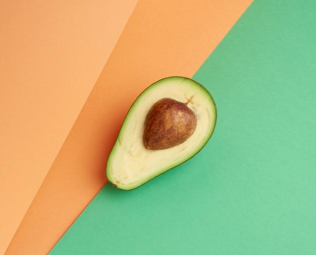Mezzo avocado verde maturo con un osso marrone su un fondo verde-arancio astratto