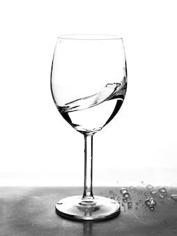 Mezzo bicchiere vuoto con acqua in movimento