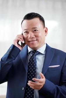 Mezzo busto dell'uomo asiatico che ha una conversazione telefonica con il socio commerciale