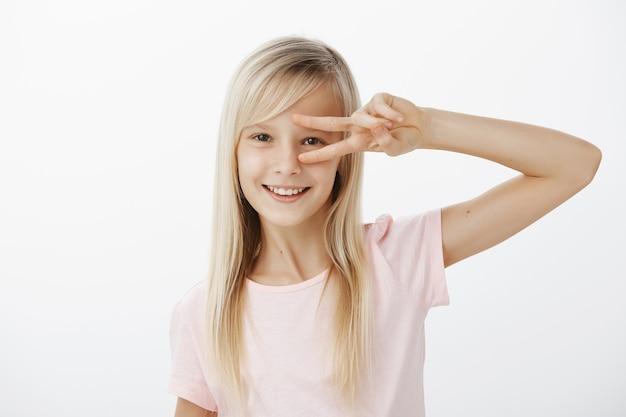 Mezzo busto di affascinante bambino positivo con i capelli biondi in abbigliamento casual, che mostra la vittoria o il gesto di pace sugli occhi e sorride felice, balla o si diverte sul muro grigio, è di ottimo umore