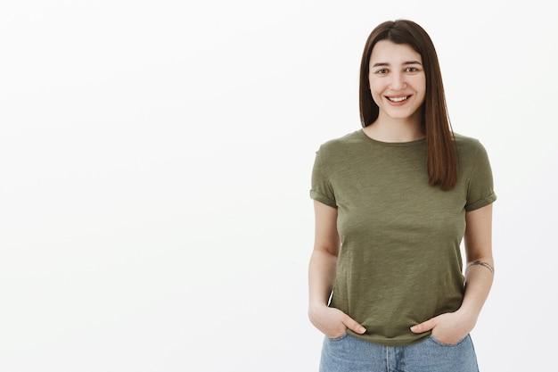 Mezzo busto di bella donna bruna brillante e sincera con acconciatura corta e sorriso amichevole che sorride tenendosi per mano in tasca in posa rilassata casual sul muro grigio