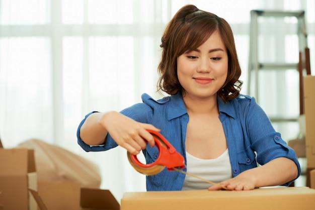 Mezzo busto di donna che applica il nastro adesivo sulla confezione