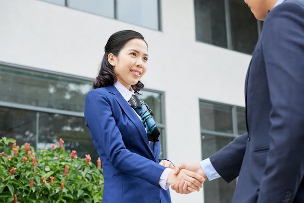 Mezzo busto di donna in abbigliamento formale che accoglie il suo irriconoscibile socio in affari con una stretta di mano