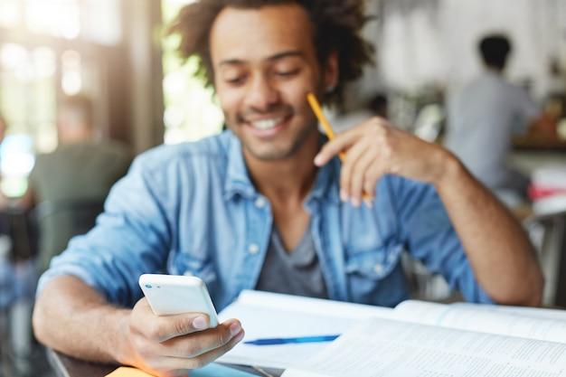 Mezzo busto di felice studente di college afroamericano con sorriso carino digitando un messaggio di testo su gadget elettronico, seduto al tavolino del bar con libri di testo. messa a fuoco selettiva sulla mano dell'uomo che tiene il telefono cellulare