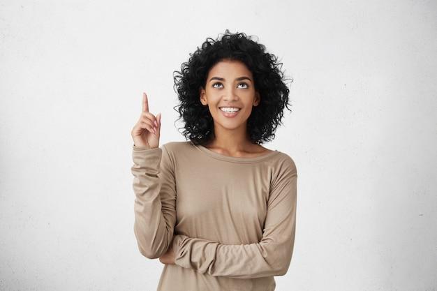 Mezzo busto di gioiosa donna che indossa t-shirt manica lunga beige alzando lo sguardo, puntando il dito allo spazio di copia sopra la sua testa. giovane donna nera che indica qualcosa