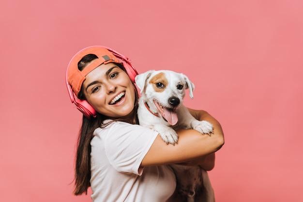 Mezzo busto di giovane femmina caucasica tiene stretto cucciolo, ride sinceramente, si rallegra presente da un amico, ama gli animali devoti