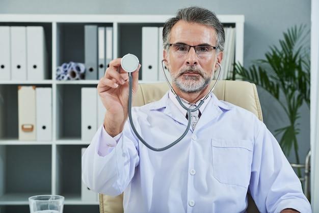 Mezzo busto di medico barbuto senior con stetoscopio rivolto verso la fotocamera