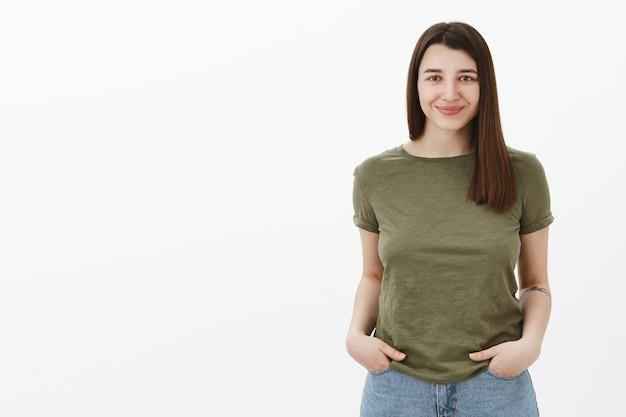 Mezzo busto di piacevole, affascinante e fiducioso giovane sviluppatore femminile 20s con tatuaggio sorridente in modo ampio e ambizioso cercando speranzoso pronto a raggiungere l'obiettivo in posa su muro grigio gioioso