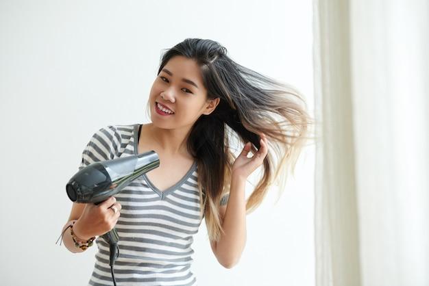 Mezzo busto di ragazza asiatica che asciuga i capelli a casa