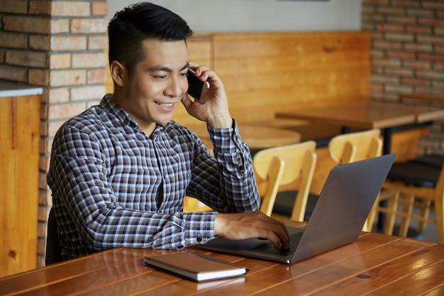 Mezzo busto di uomo che lavora al computer portatile mentre parla al telefono