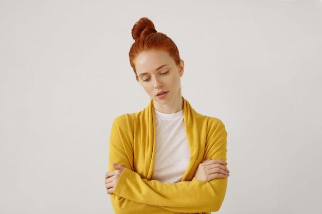 Mezzo busto ritratto di splendida giovane donna caucasica con lineamenti delicati e capelli rossi che guarda in basso con triste espressione infelice con le braccia incrociate