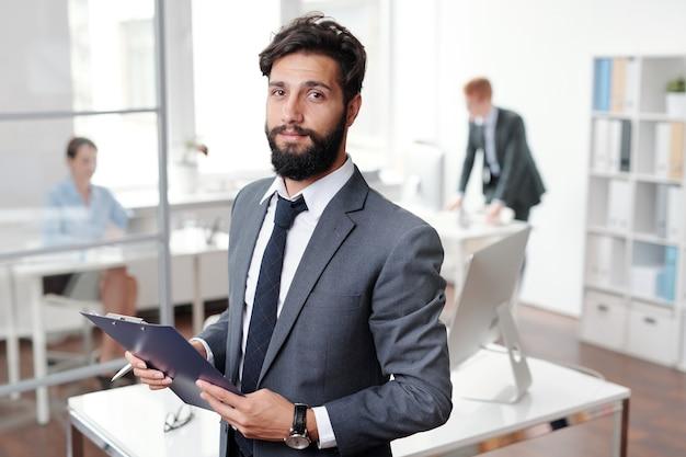 Mezzo busto ritratto di uomo d'affari barbuto bello e tenendo appunti mentre posa in ufficio, copia dello spazio