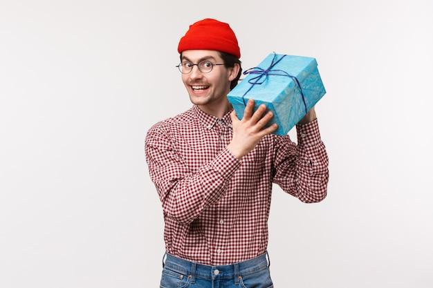 Mezzo busto ritratto felice ed eccitato carino ragazzo barbuto che prova a indovinare cosa c'è dentro la scatola, scuotendo il regalo avvolto curioso che amico gli dia per il b-day, sorridendo felice e allegro, stand