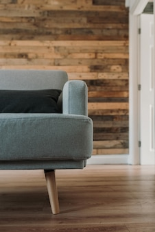 Mezzo colpo alto vicino di verticale di un sofà grigio con un cuscino nero su