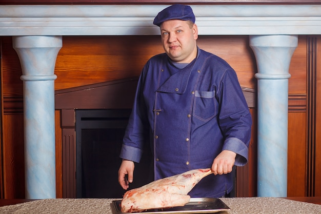 Mezzo colpo di spicco dello chef maschio premuroso, detiene un grosso pezzo di carne crudo rosso