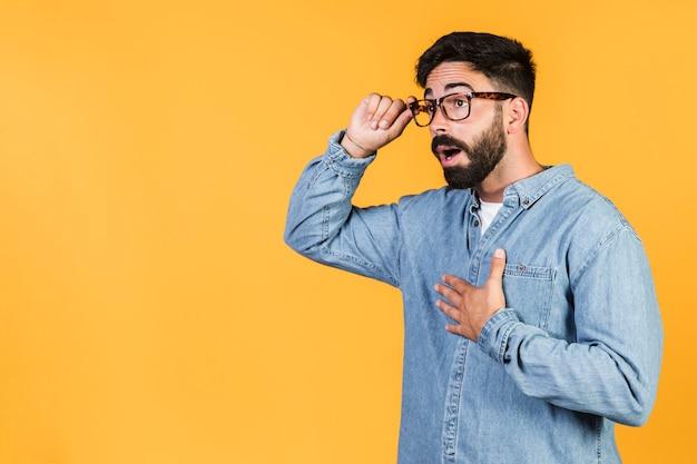 Mezzo colpo ragazzo scioccato tenendo i suoi occhiali