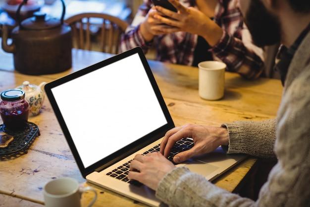 Mezzo sezione dell'uomo che per mezzo del computer portatile