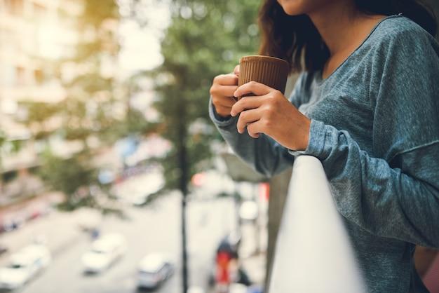 Mezzo sezione della donna che beve tè che sta sul balcone