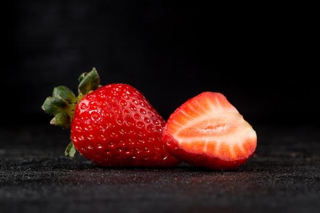 Mezzo taglio della frutta morbida succosa fresca rossa della fragola isolato su gray