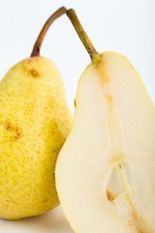 Mezzo taglio succoso dolce giallo pera isolato sul pavimento bianco
