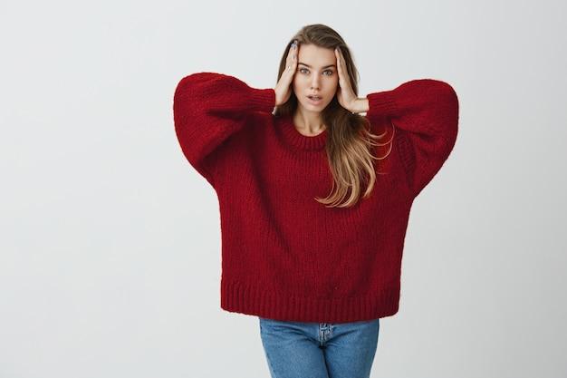 Mi gira la testa. ritratto di donna sensuale espressiva con aspetto attraente in piedi in maglione sciolto rosso, tenendosi per mano sul viso e facendo espressione modello