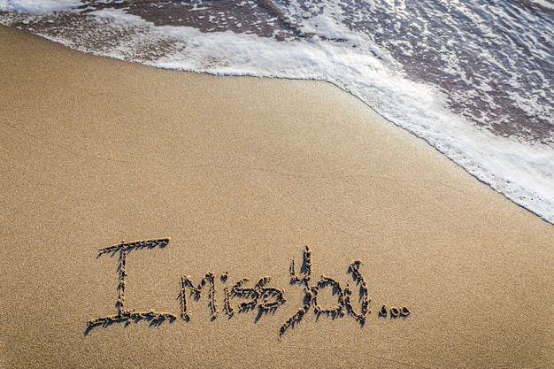 Mi manchi. mancanza amorevole scritta sulla sabbia